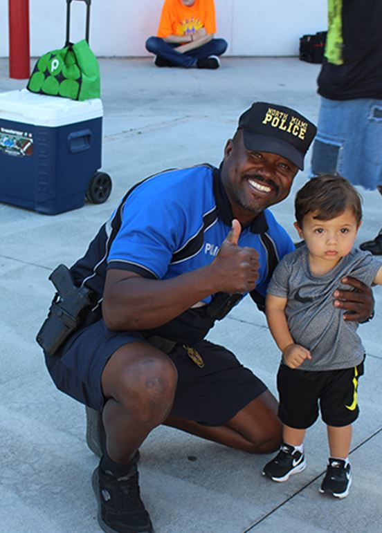 Officer posing with small kid