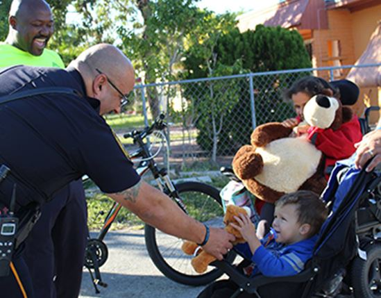Officer giving child a stuffed animal