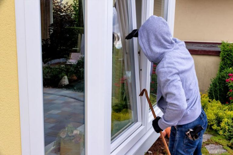 Person in hoodie holding a crowbar looking into a window